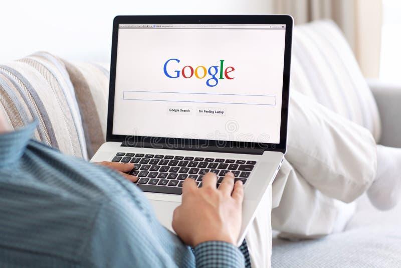 Укомплектуйте личным составом сидеть на сетчатке MacBook с местом Google на экране стоковое изображение
