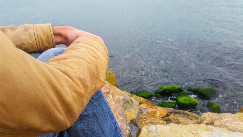 Укомплектуйте личным составом сидеть на утесах, наблюдая море стоковое изображение rf