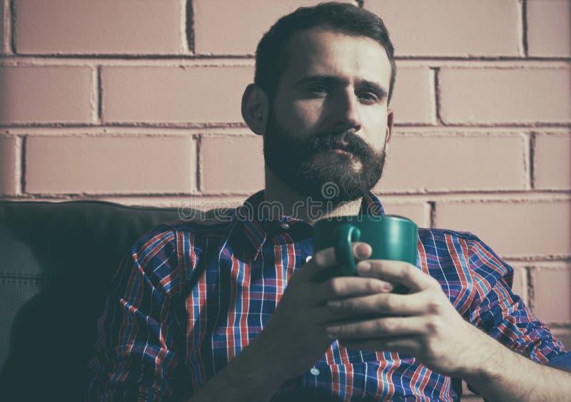Укомплектуйте личным составом сидеть с чашкой кофе или чая утра стоковые изображения