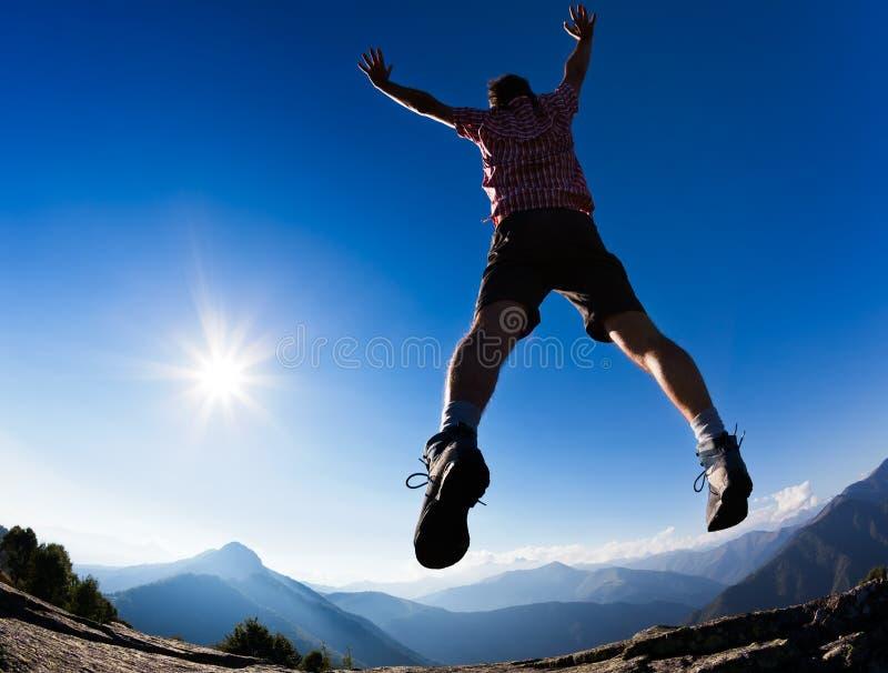 Укомплектуйте личным составом скакать в солнечность против голубого неба стоковое фото rf