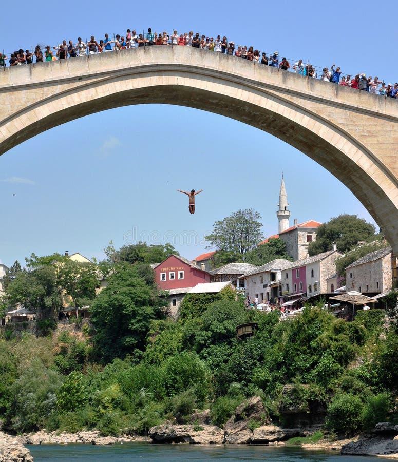 Укомплектуйте личным составом скакать от моста в старом городке Мостара стоковые изображения