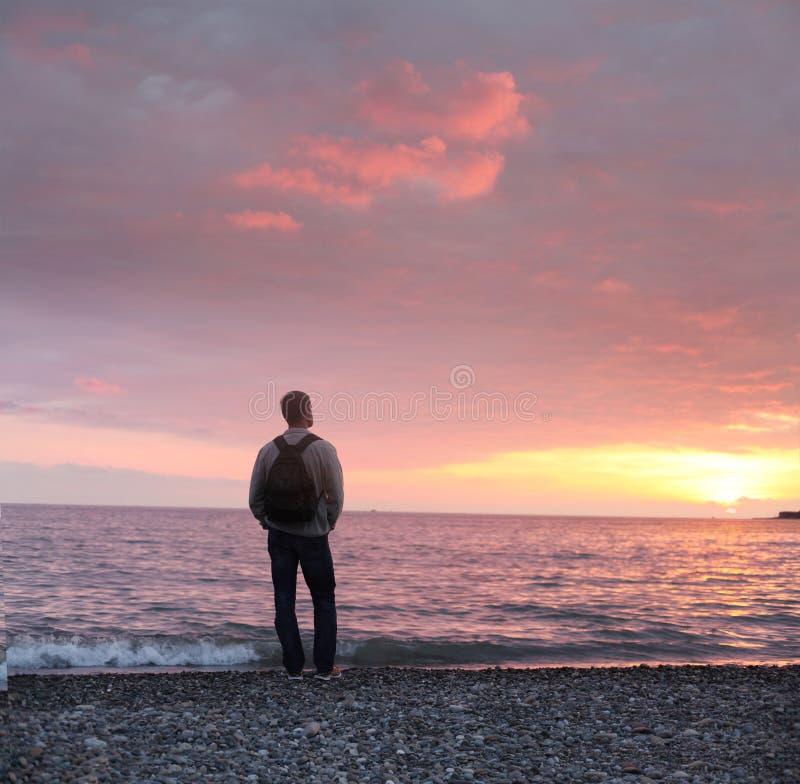 Укомплектуйте личным составом смотреть заход солнца на пляже стоковая фотография rf