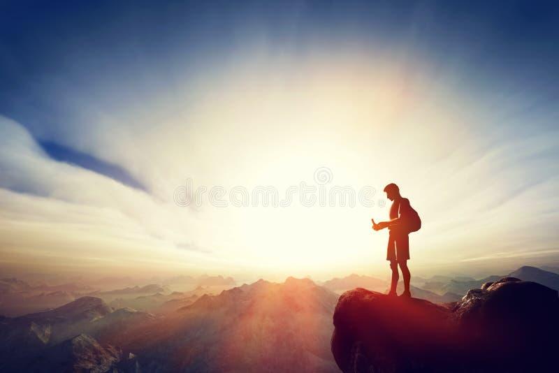 Укомплектуйте личным составом соединяться с его smartphone na górze горы Связь стоковое изображение rf