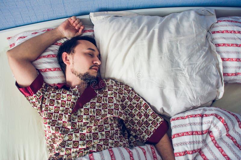 Укомплектуйте личным составом спать в его кровати на белой подушке стоковые изображения