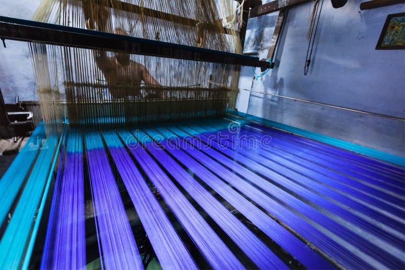 Укомплектуйте личным составом сплетя silk сари на тени в Индии стоковые фото