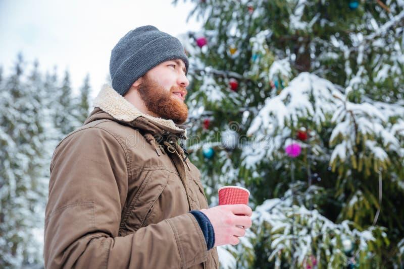 Укомплектуйте личным составом стоящую близко украшенную рождественскую елку и выпивая кофе outdoors стоковые изображения rf