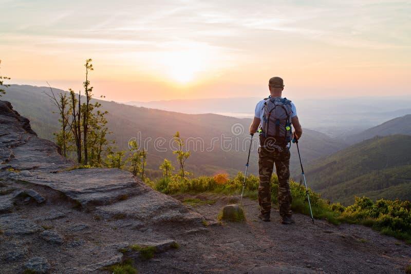 Укомплектуйте личным составом туриста с trekking поляками наблюдая красивый восход солнца стоковое фото rf