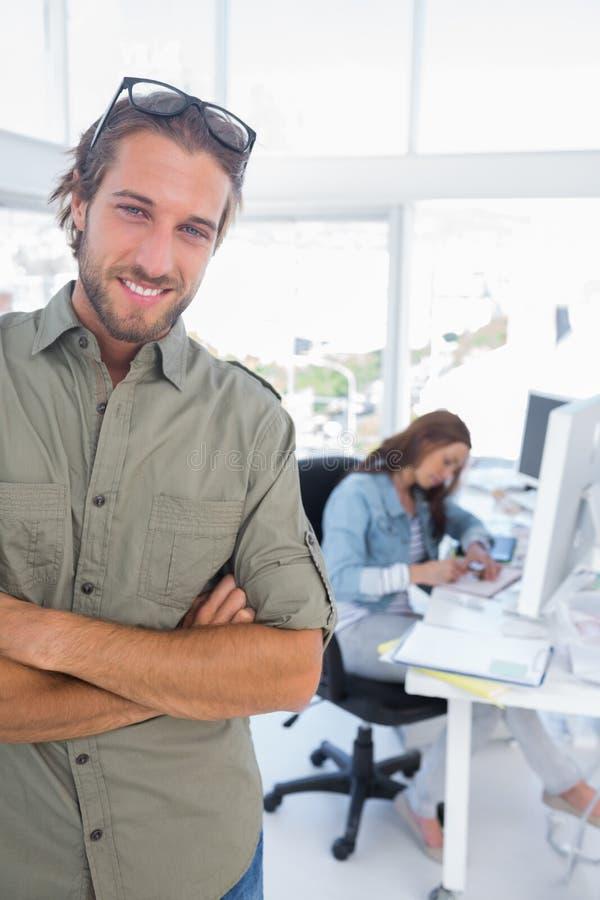 Укомплектуйте личным составом усмехаться в творческом офисе при сложенные оружия стоковое изображение