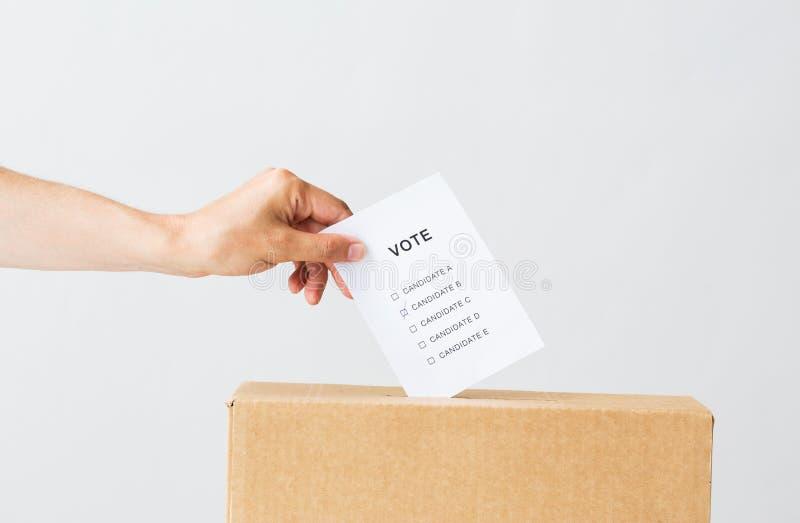 Укомплектуйте личным составом установку его голосования в урну для избирательных бюллетеней на избрание стоковые фото