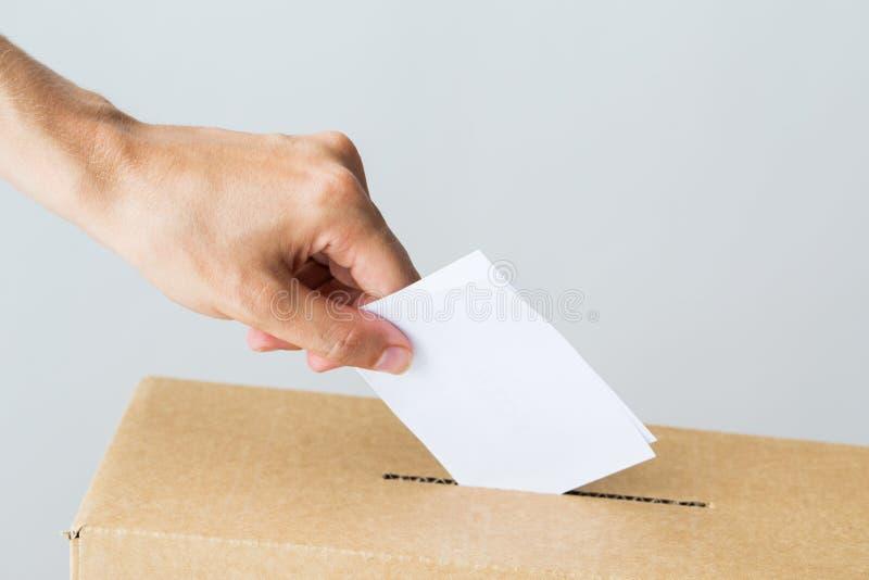 Укомплектуйте личным составом установку его голосования в урну для избирательных бюллетеней на избрание стоковые изображения