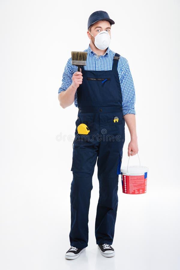Укомплектуйте личным составом художника в защитной маске держа ведро краски и почистьте щеткой стоковая фотография rf