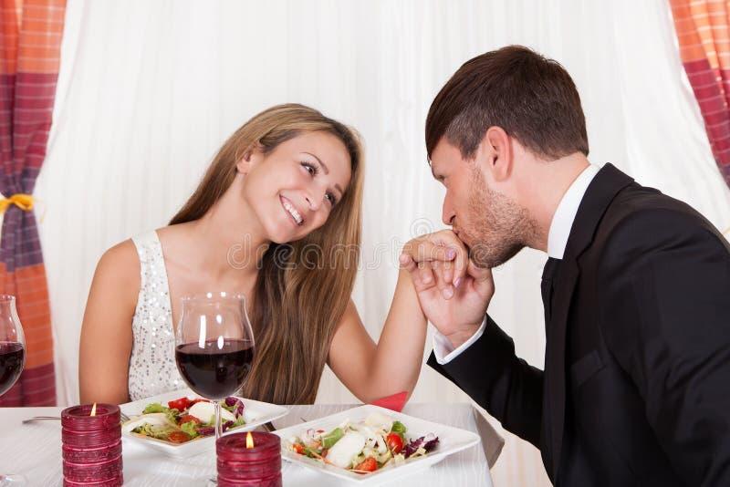 Укомплектуйте личным составом целовать руку женщины на романтичном обедающем стоковое изображение rf