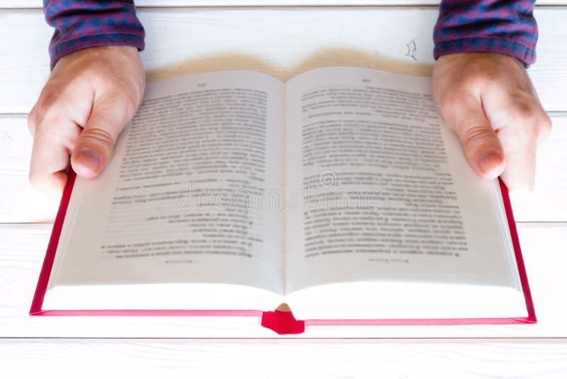 Укомплектуйте личным составом читать книгу на белой деревянной предпосылке стоковое изображение