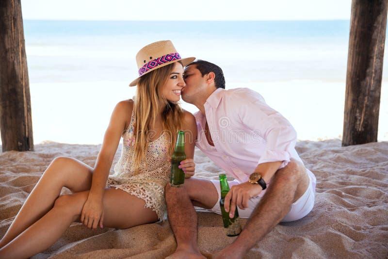 Укомплектуйте личным составом шептать в ухе подруги на пляже стоковое фото