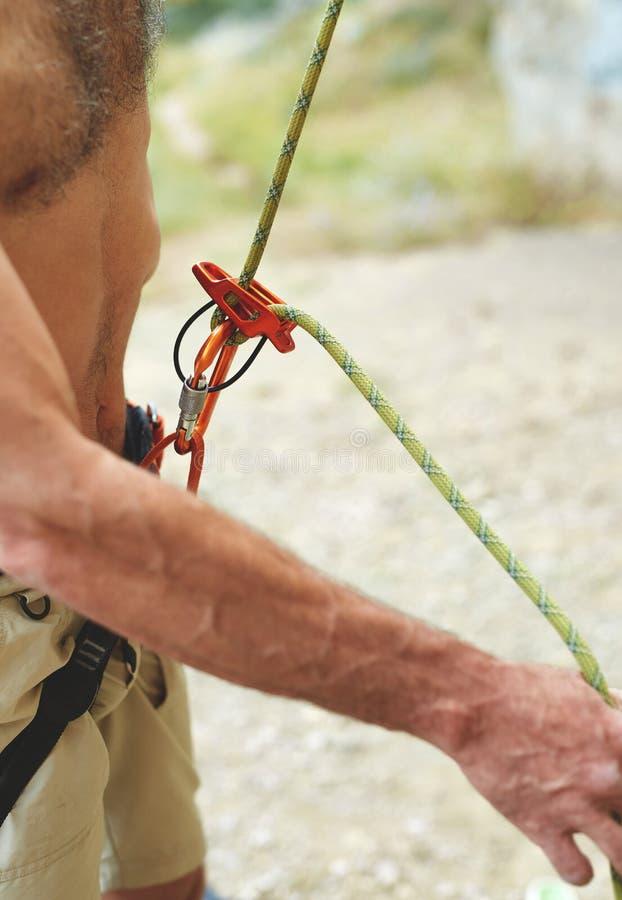 Укомплектуйте личным составом belaying другой альпинист через прибор belay стоковые изображения