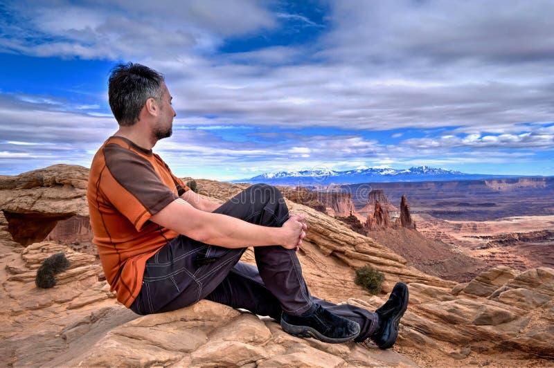 Укомплектуйте личным составом hiker на скале смотря взгляды каньона стоковая фотография