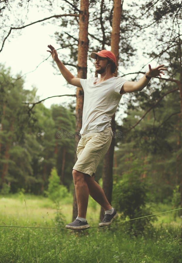 Укомплектуйте личным составом slacklining идти и балансировать на веревочке, slackline в лесе стоковые изображения