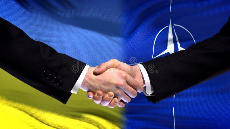 Украина и рукопожатие НАТО, международные отношения приятельства, предпосылка флага стоковое изображение