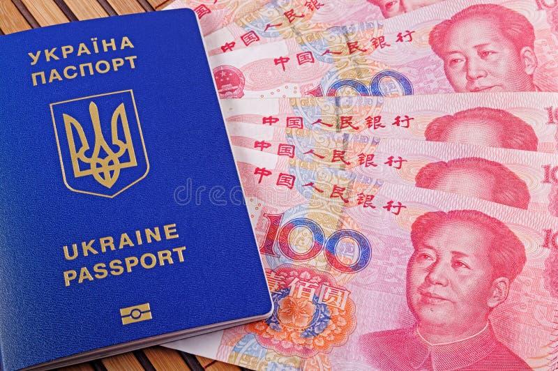 Украинские паспорт и Юани на предпосылке бамбуковой циновки стоковые фото