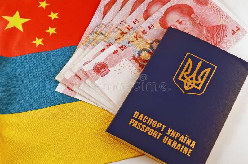 Украинские паспорт и Юани на предпосылке флагов Украины и Китая стоковое изображение rf