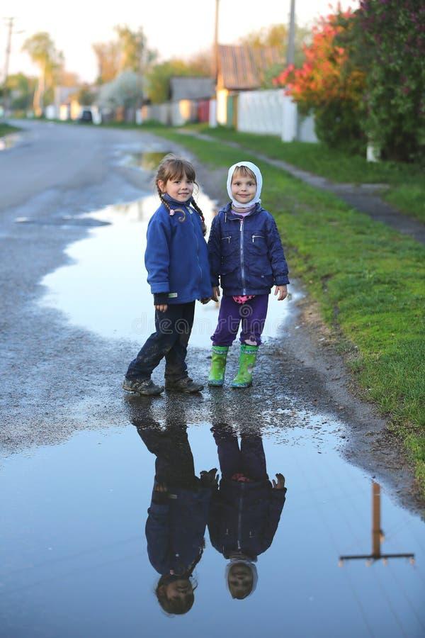 Украин, Киев 2 малых друз стоят на проселочной дороге около большой лужицы стоковое изображение