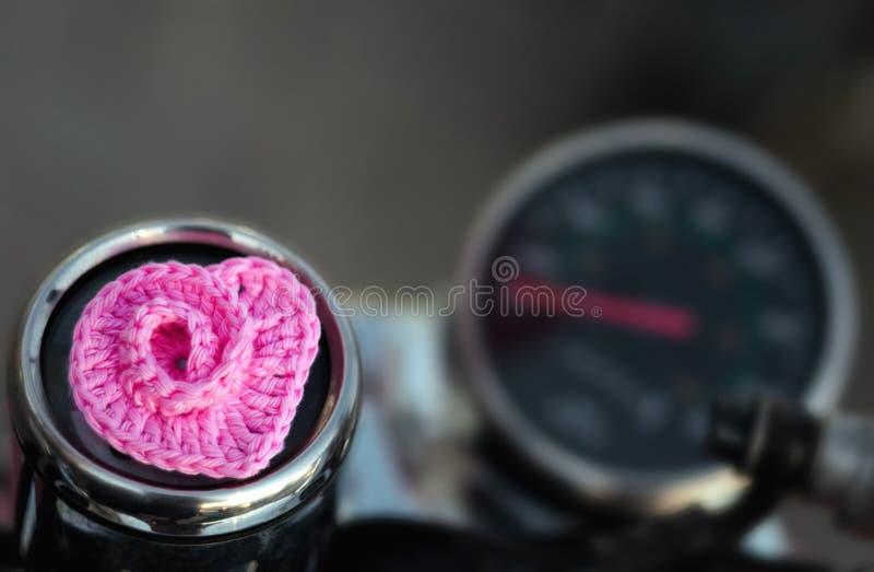 Украсьте дырочками вязать крючком крючком спиральные лож сердца на мопеде на предпосылке спидометра стоковое изображение