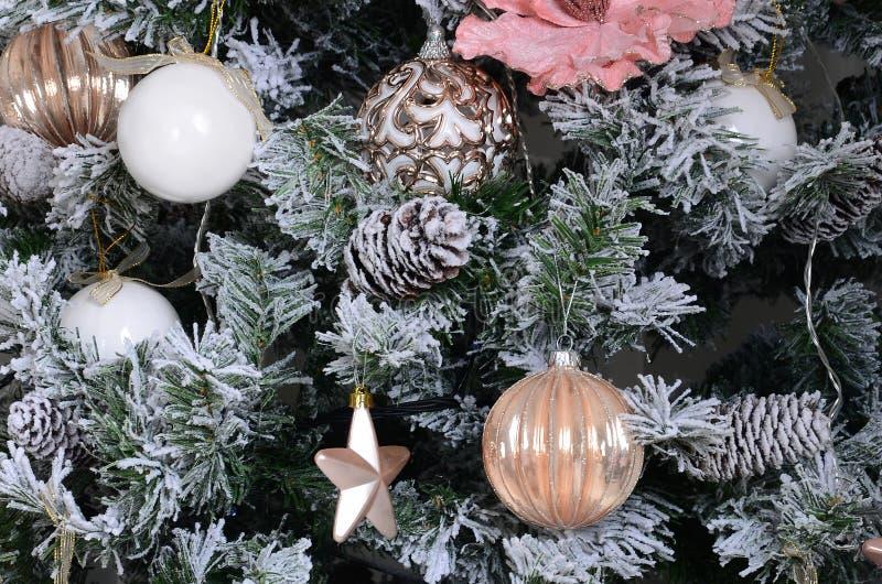 Украшать поднимающее вверх рождественской елки близкое Шарик украшения, снежная зеленая ель, розовые игрушки x-mas и света Польза стоковые изображения
