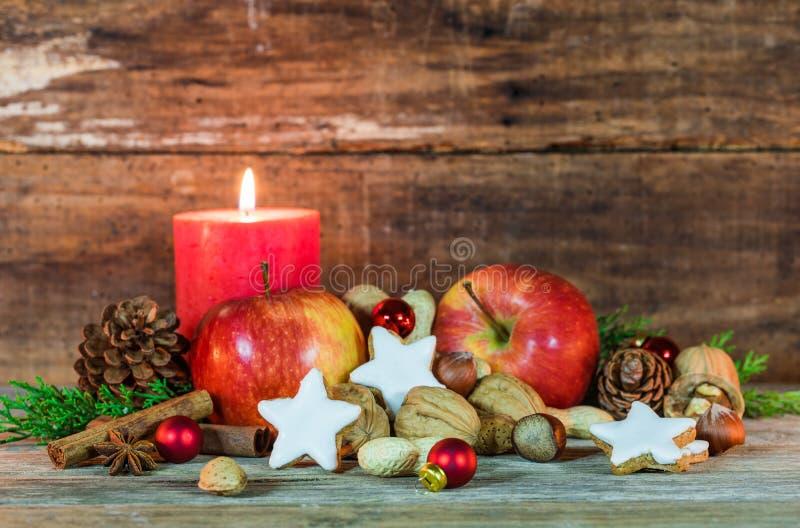 Украшение еды рождества с красными специями яблок, печений звезды, чокнутого и ароматичных с свечой и деревянной предпосылкой стоковое фото