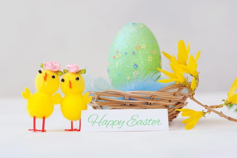 Украшение пасхи с цыпленком, зеленым пасхальным яйцом в корзине на белой предпосылке стоковое фото