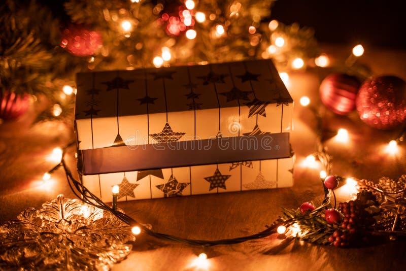 Украшение подарочных коробок рождества с рождественской елкой и свечой освещает на деревянном столе с светами bokeh стоковые фото