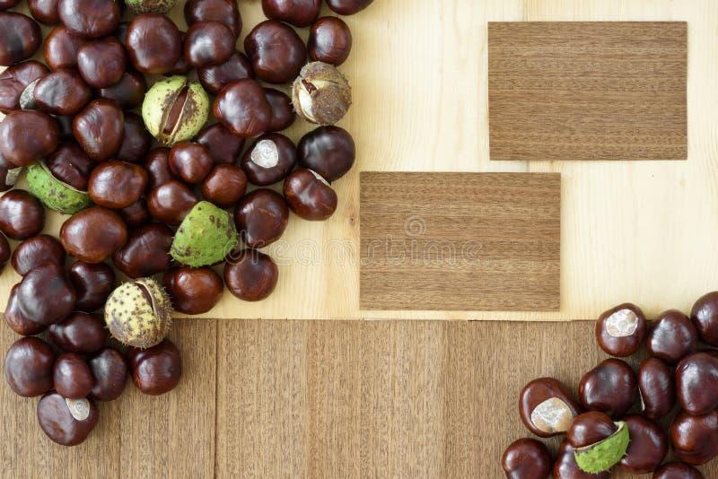 Украшение природы осени в коричневом цвете аранжированном от каштанов и деревянных карт, всех на деревянной предпосылке стоковые изображения rf