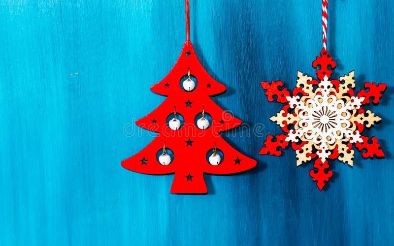 Украшение рождества вися над деревянной голубой предпосылкой, рождественской открыткой стоковые изображения