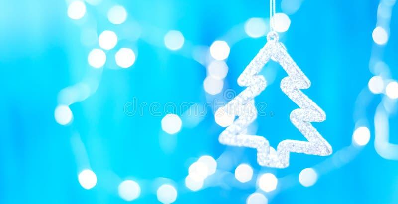 Украшение рождества вися над деревянной голубой предпосылкой, рождественской открыткой стоковая фотография rf