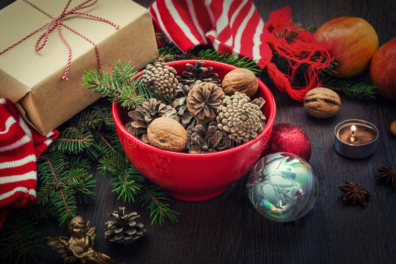 Украшение рождества - красный шар вполне ель-конусов, подарочной коробки обернутой в бумаге kraft, ветвях сосны, свече, гайках, а стоковые изображения rf
