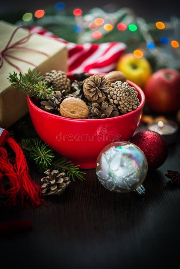 Украшение рождества - красный шар вполне ель-конусов, подарочной коробки обернутой в бумаге kraft, ветвях сосны, свече, гайках, а стоковая фотография rf