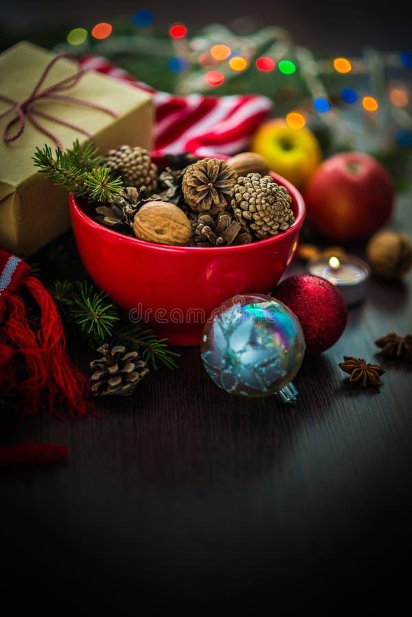 Украшение рождества - красный шар вполне ель-конусов, подарочной коробки обернутой в бумаге kraft, ветвях сосны, свече, гайках, а стоковые фотографии rf