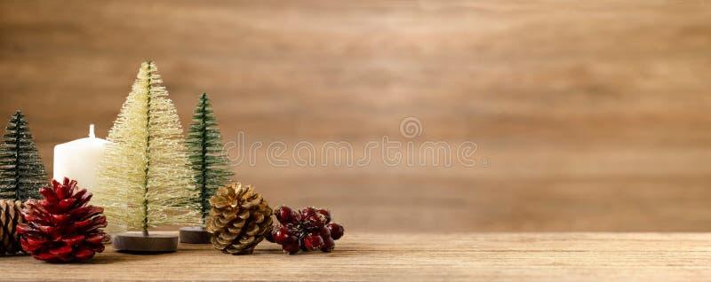 Украшение рождественской елки на деревянной таблице со снегом конус сосны, омела и шарик колокола вися с предпосылкой стены нерез стоковое фото