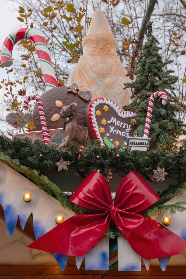 Украшение рождества на рынке X-mas: белая диаграмма Санта Клауса, декоративные большие тросточки конфеты, ель и пряник шоколада стоковые изображения rf
