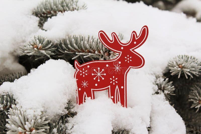 Украшение рождественской елки красный олень (лось) на снеге на ели стоковые изображения