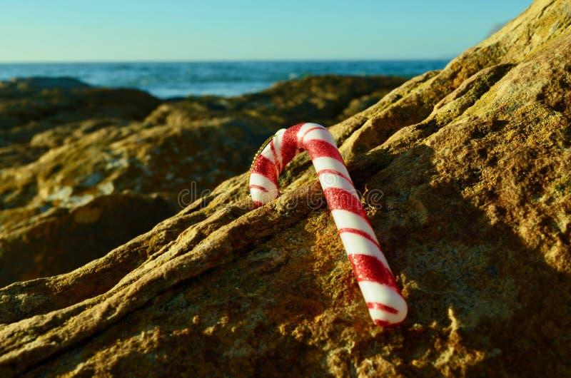 Украшение ручки тросточки красного и белого рождества на утесах рождеством моря в июле стоковое изображение