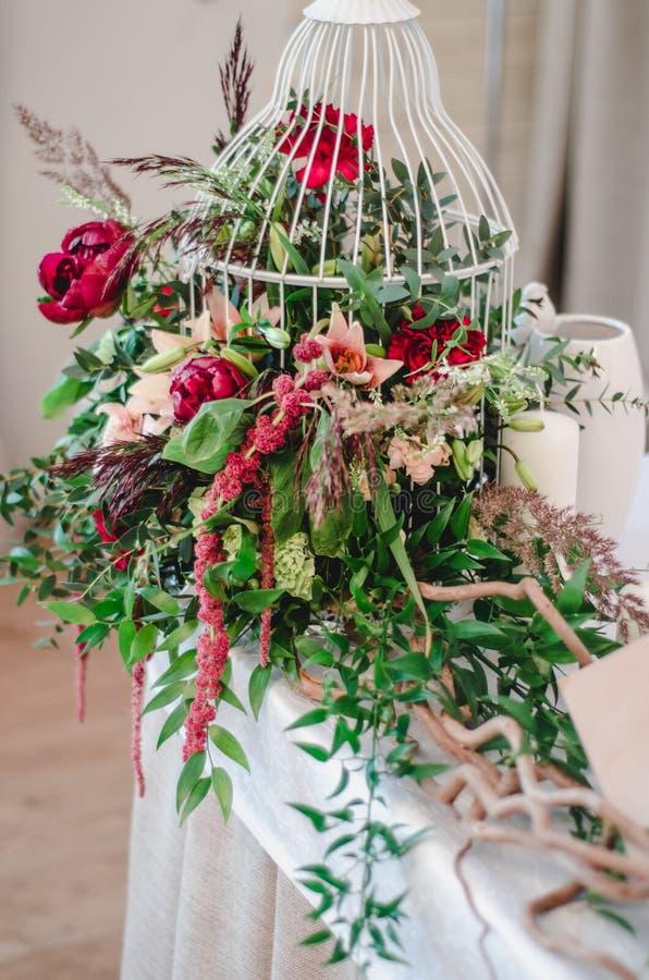 Украшение свадебной церемонии в restoraunt Состав красных и розовых пионов, розовых цветков, зеленого цвета евкалипта стоит на та стоковое изображение