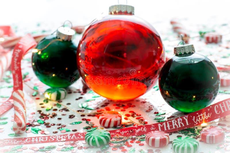 Украшение с красной жидкостью заполнило шарик орнамента рождества и 2 зеленых заполненных шарика орнамента окруженного красным цв стоковое фото rf