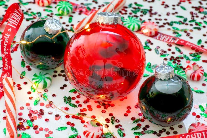 Украшение с красной жидкостью заполнило шарик орнамента рождества и 2 зеленых заполненных шарика орнамента окруженного красным цв стоковое фото