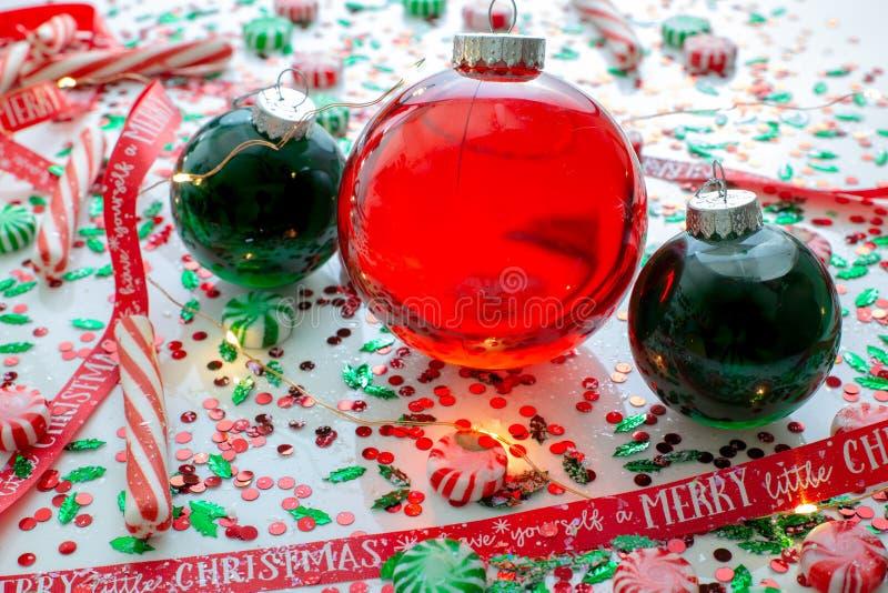 Украшение с красной жидкостью заполнило шарик орнамента рождества и 2 зеленых заполненных шарика орнамента окруженного красным цв стоковая фотография rf