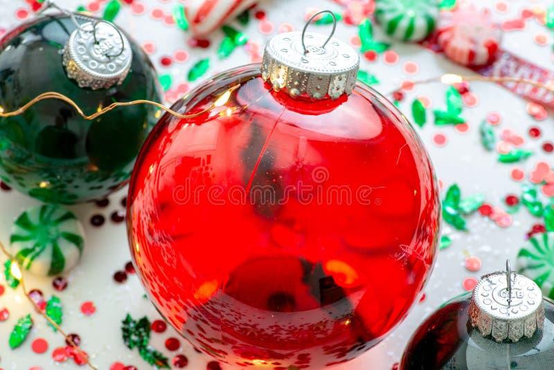 Украшение с красной жидкостью заполнило шарик орнамента рождества и 2 зеленых заполненных шарика орнамента окруженного красным цв стоковые фотографии rf