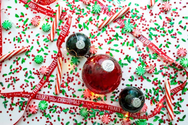 Украшение с красной жидкостью заполнило шарик орнамента рождества и 2 зеленых заполненных шарика орнамента окруженного красным цв стоковые изображения