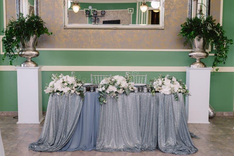 Украшение таблицы свадьбы в цветах белизны и серебра для жениха и невесты стоковые фотографии rf