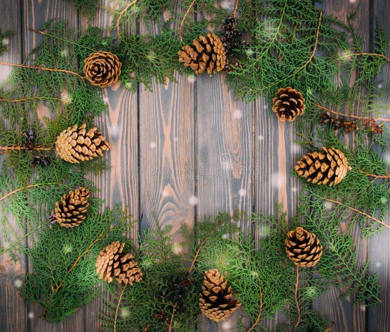 Украшения зимы праздничные Рождественская открытка с конусами ели и деревянной предпосылкой стоковая фотография rf