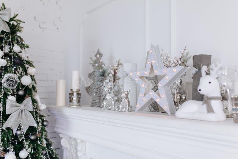 Украшения рождества и Нового Года белые и серебряные на камине в белой внутренней комнате с деревом Нового Года Концепция Xmas стоковое фото rf
