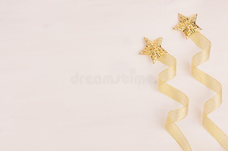 Украшения рождества, фейерверк звезд золота и лента скручиваемости на мягкой белой деревянной предпосылке стоковое изображение rf